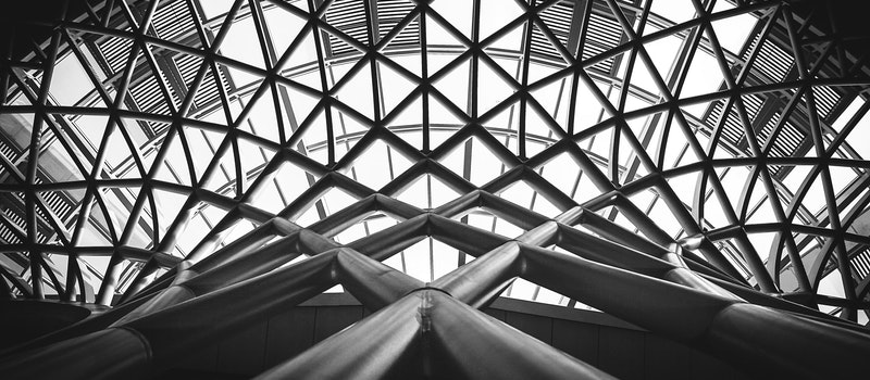 low-angle-photography-of-metal-building-on-grayscale